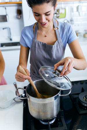 Portrait of beautiful young woman cooking soup with vegetables at home.