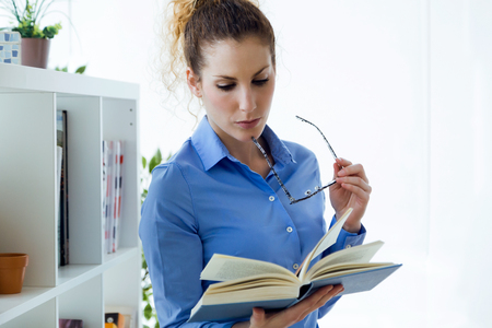 Portrait of beautiful young woman reading a book at home.