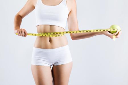 Retrato de mujer midiendo su cuerpo delgado. Aislado sobre fondo blanco.