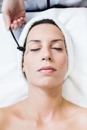 Portrait of beautiful young woman receiving antiaging treatment in spa.
