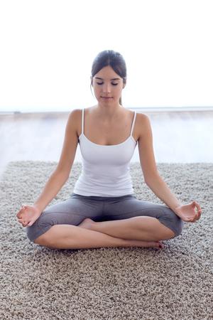 Retrato de mujer joven hermosa haciendo ejercicios de yoga en casa.