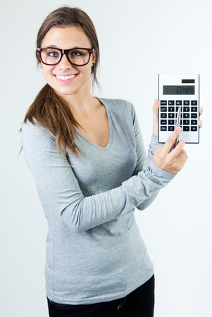 Studio Portrait of beautiful young woman posing with calculator