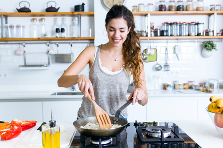 Portrait of young woman frying onion into the pan in the kitchen.