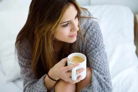 Portrait of beautiful young woman drinking coffee on bed.