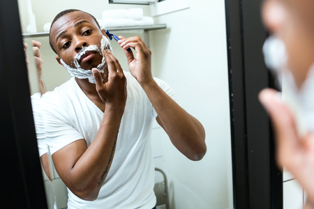 Portrait of handsome young black man shaving in home bathroom.