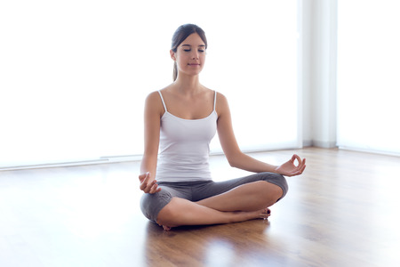 Portrait of beautiful young woman doing yoga exercises at home. Banco de Imagens - 111625351