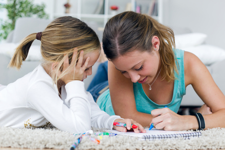 Portrait of young mother and daughter drawing on the notebook at home.