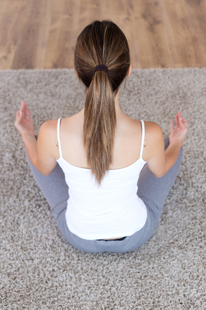 Portrait of beautiful young woman doing yoga exercises at home. Banco de Imagens