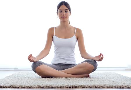 Ritratto di bella giovane donna che fa esercizi di yoga a casa.
