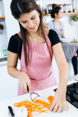 Portrait of beautiful young woman cutting carrots in the kitchen.