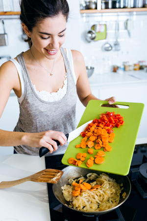 Portrait of young woman frying vegetables into the pan.