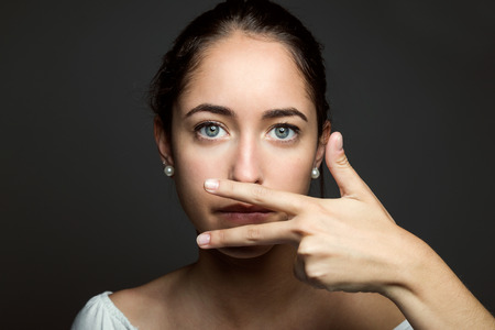 Portrait of beautiful young woman covering her mouth with hand. Isolated.