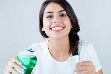 Portret pięknej dziewczyny za pomocą płynu do płukania ust. Na białym tle. Zdjęcie Seryjne