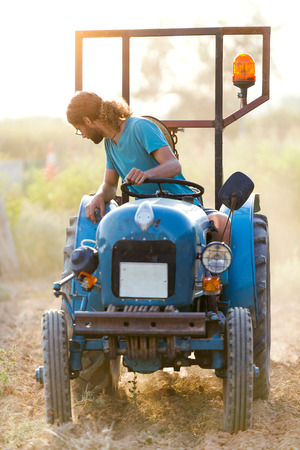 Shot of young hipster farmer in tractor preparing land with seed cultivator in the garden. Stok Fotoğraf - 111656167