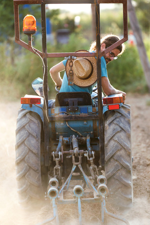 Shot of young hipster farmer in tractor preparing land with seed cultivator in the garden.