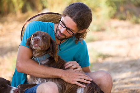 Shot of young hipster man caressing and having fun with a dog in the garden. Stock fotó
