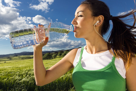 Woman drinking water after sport activities in the countryside