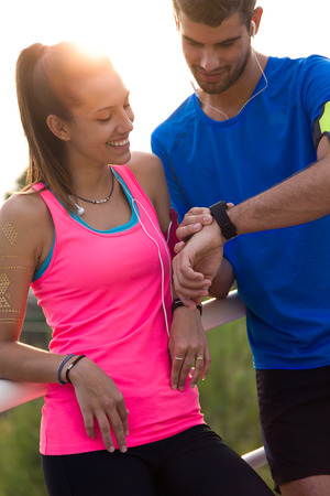 Outdoor portrait of young couple using they smartwatch after running. Stock Photo