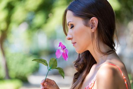 Portrait of young beautiful girl smells flowers, against green summer garden. Stock fotó