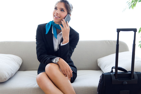 Portrait of beautiful hostess in airport with mobile phone. Stock Photo