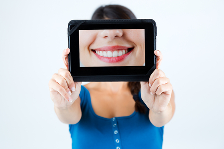 Portrait of beautiful girl holding a picture of a mouth smiling.