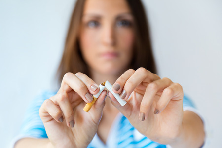 Porträt der jungen Frau weigert sich zu rauchen und bricht Zigarette. Standard-Bild