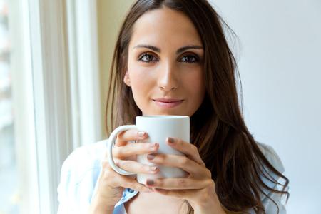 Portrait of beautiful woman drinking coffee in the morning near the window.