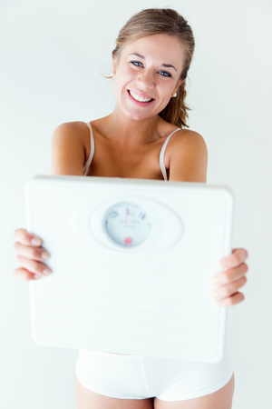 Portrait of young girl in underwear holding scale. Stock Photo