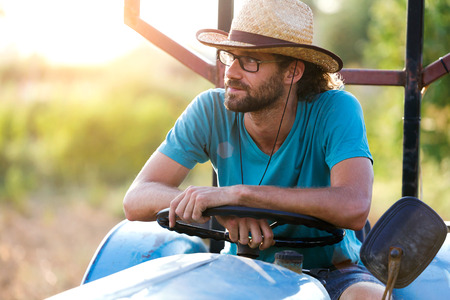 Shot of young hipster farmer in tractor looking for his harvest in the garden. Stok Fotoğraf - 111737203