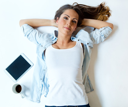 Portrait of overhead view of young woman lying on back on carpet alongside laptop and coffee. Stock Photo