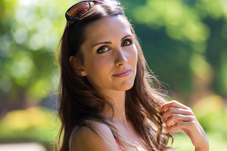 Portrait of beautiful woman with dark hair and brown eyes posing at summer garden.