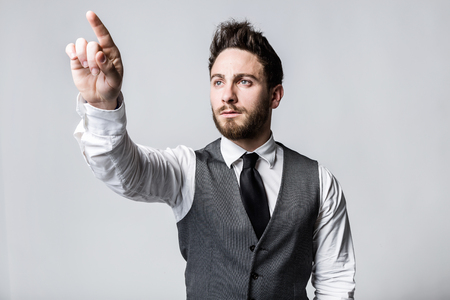 Portrait of young businessman pressing a button on an imaginary screen. Stock Photo