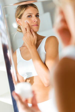 Portrait d'une belle jeune femme prenant soin de sa peau debout près du miroir dans la salle de bain. Banque d'images