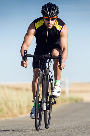 Portrait of handsome young man cycling on the road. Stockfoto - 111739117