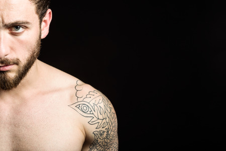 Portrait of handsome young man with tattoos posing. Isolated on black. Banque d'images - 111739312