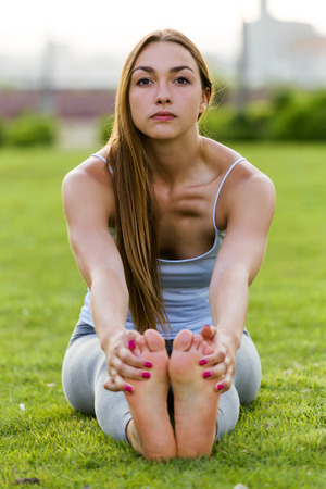 Portrait of beautiful young woman doing yoga in the street.