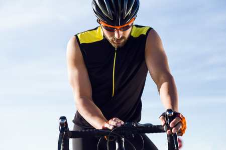 Portrait of young cyclist man setting timer on bicycle in sports gear. Reklamní fotografie - 111739477