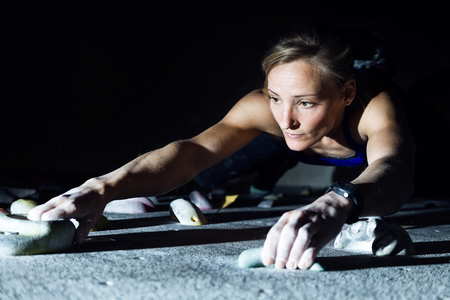Portrait of fit woman rock climbing indoors at the gym.