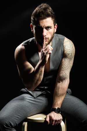Portrait of handsome young man with tattoos making a silence gesture. Stock Photo - 111739857