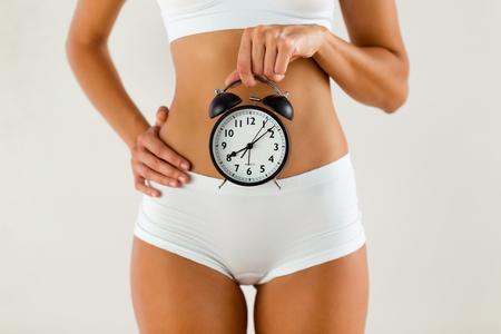 Gros plan d'une jeune femme tenant une horloge sur fond blanc isolé.