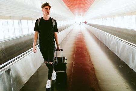Portrait of handsome young man walking in the airport.