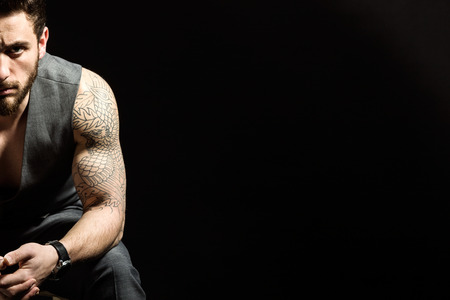 Portrait of handsome young man with tattoos posing. Isolated on black. Banque d'images - 111740264