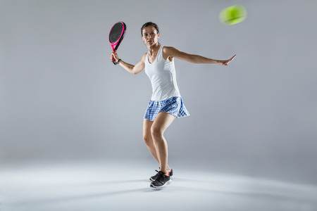Shot of adult fitness woman playing padel indoor. Isolated on white.