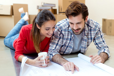 Portrait of Young couple looking at the blueprints of their new home Stockfoto - 111740294