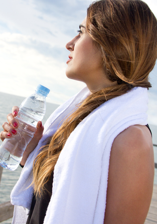 Young Woman drinking water after sport activities