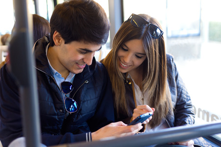 Portrait of young couple using mobile phone at bus. Imagens