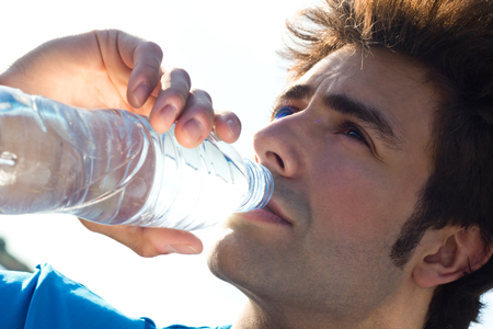 Young Man drinking water after sport activities