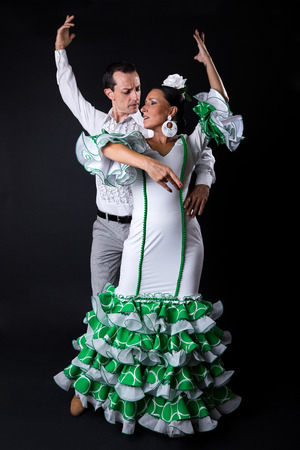 Portrait of young flamenco dancers in beautiful dress on black background.