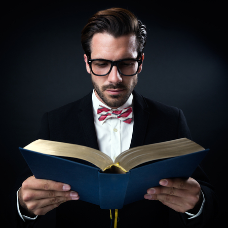 Portrait of intrigued businessman with glasses reading a book. Isolated on black.