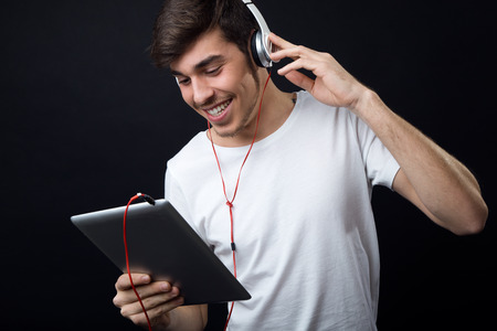 Portrait of young beautiful man listening to music. Isolated on black. Stock Photo